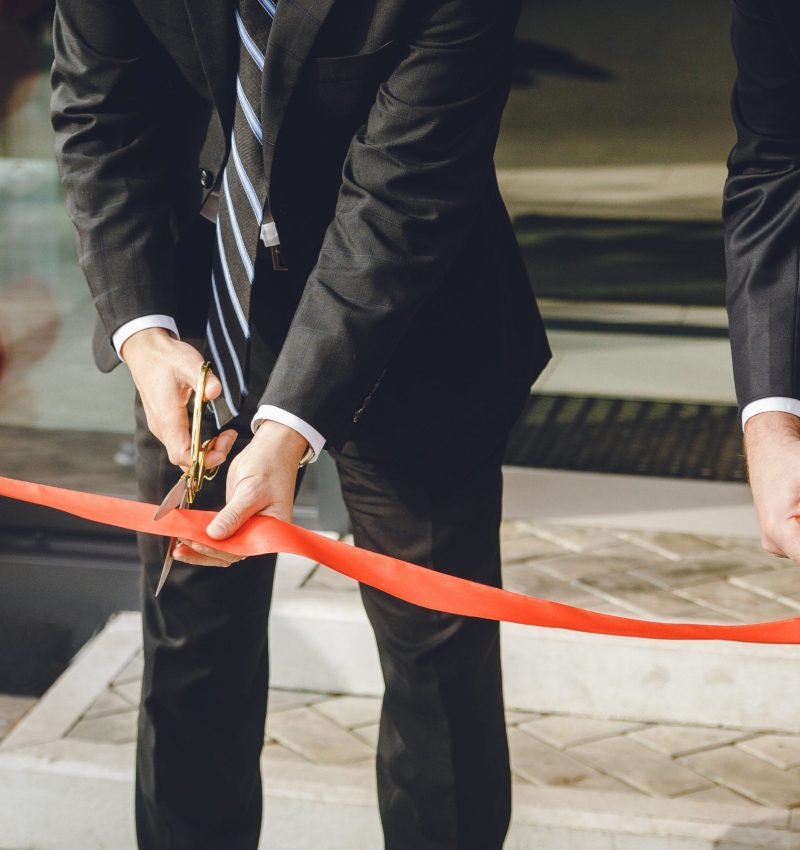 Businessman cutting red ribbon with pair of scissors. Two man in a classic black official suit cuts a red tape opening place